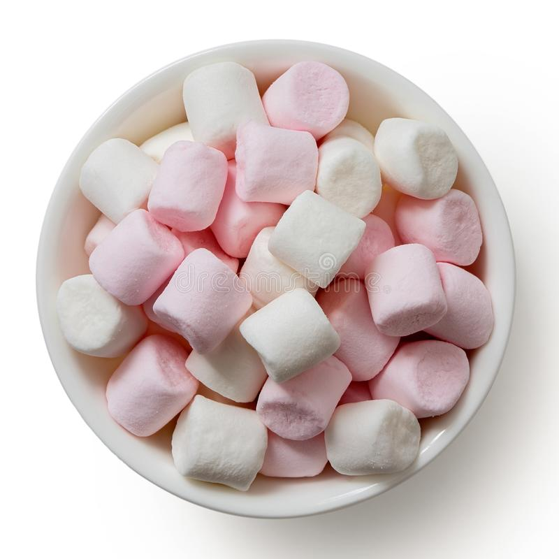 Pink and white mini marshmallows in white ceramic dish isolated on white from above.  royalty free stock photo