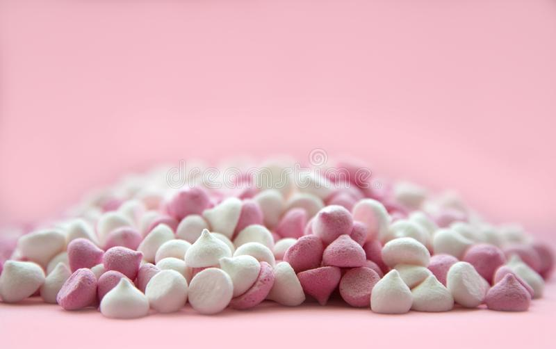 Pink and white mini meringues in the shape of drops, which lie on a pink background. Place for text stock photo