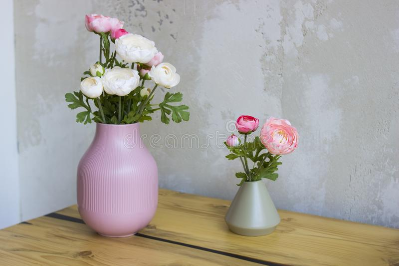Pink and white peonies in a vase on a wooden table. royalty free stock photography