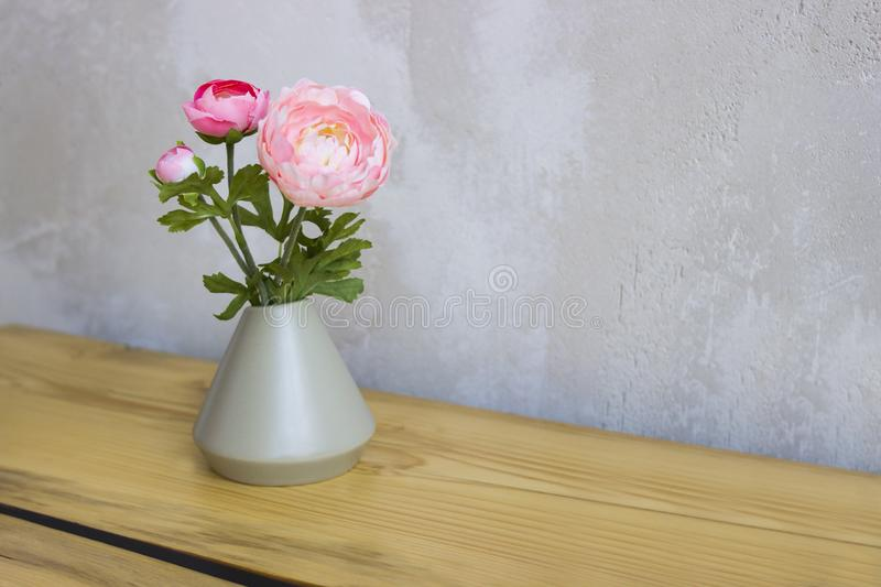 Pink and white peonies in a vase on a wooden table. stock photos