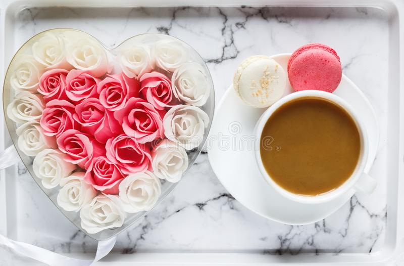 Pink and white roses in heart shaped box and coffee cup on marble table background. Delicious sweets and coffee break. Gift, present for Valentines, Mothers royalty free stock image