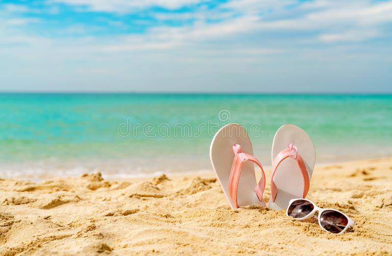 Pink and white sandals, sunglasses on sand beach at seaside. Casual fashion style flipflop and glasses. Summer vacation. On tropical beach. Fun holiday travel stock photo