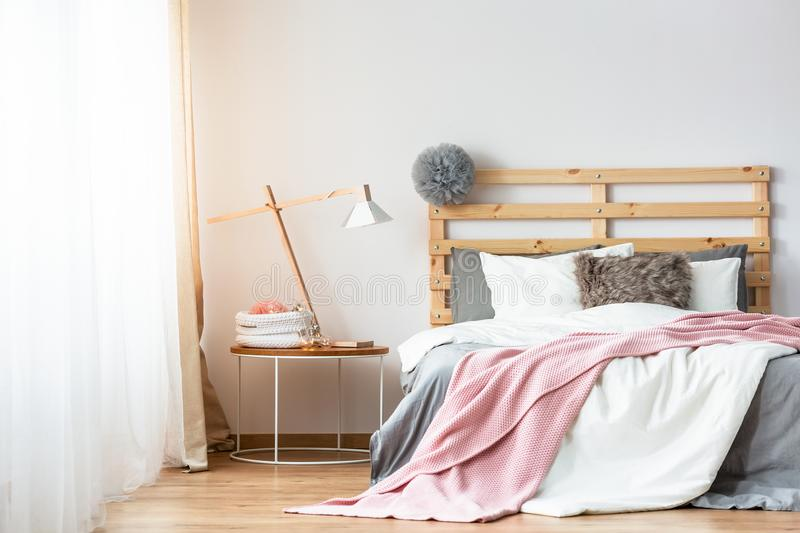 Pink and white sheets on wooden bed next to table with lamp in p stock photo