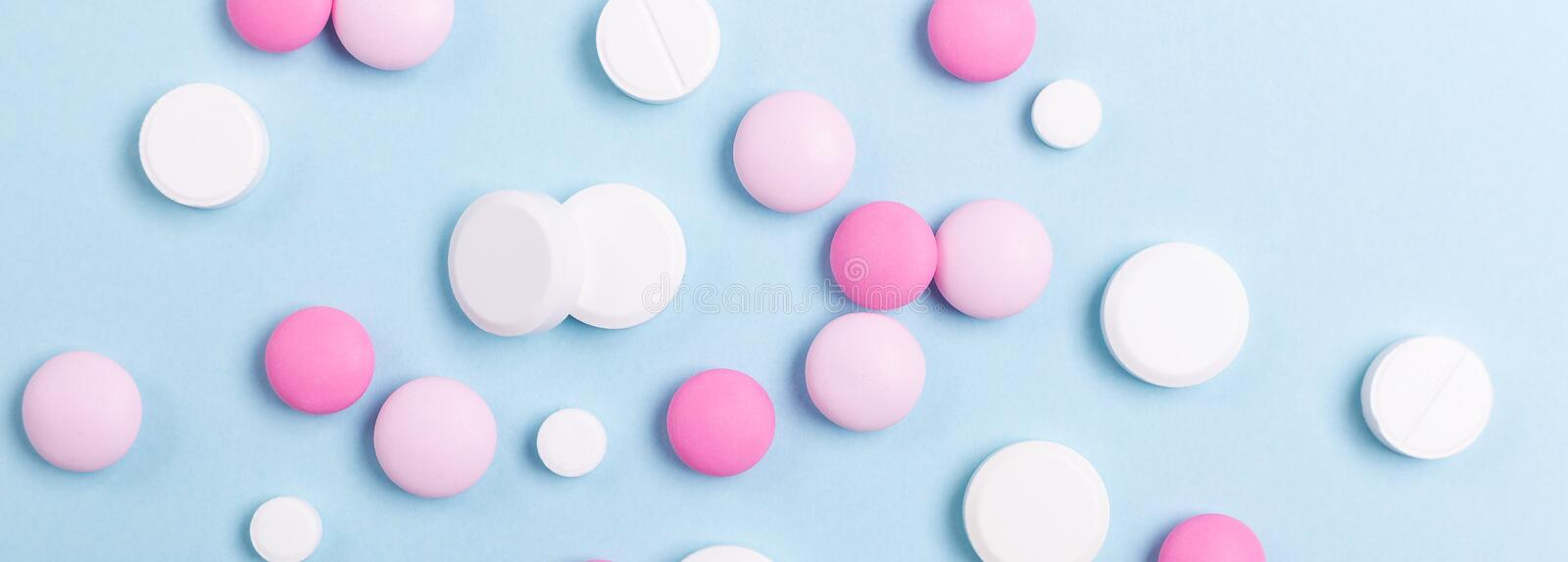Pink and white tablets on blue background Heap of assorted various medicine tablets Horizontal banner stock photography