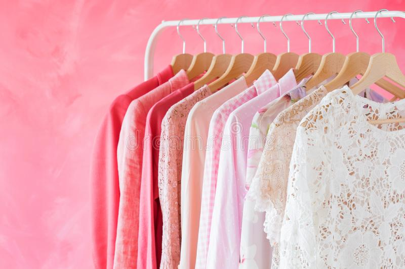 Pink women clothes hanging on rack royalty free stock photography