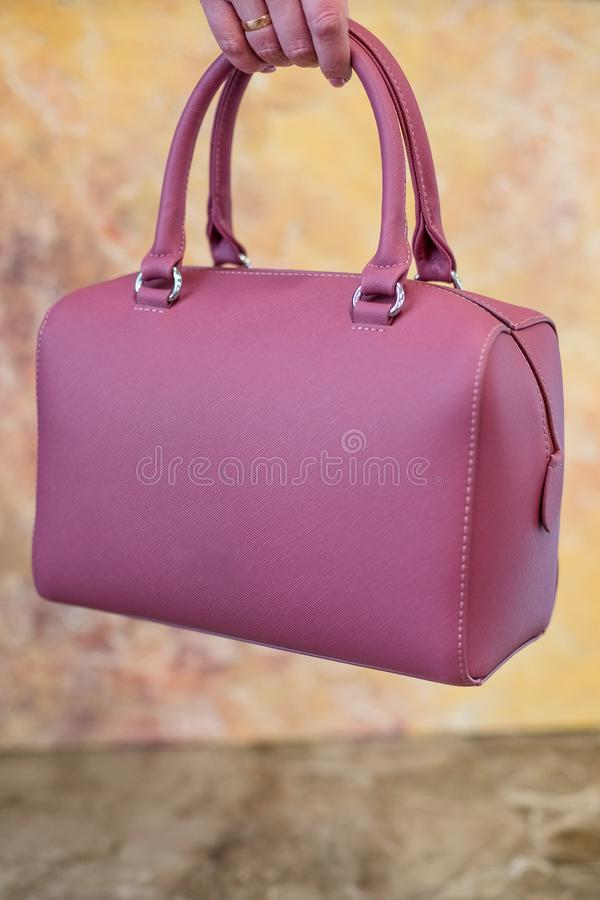 Pink Women`s handbag in hand, Ladies bag, Pink female clutch,Pink clutch.Women`s bag isolated on marble background. Pink Women`s handbag in hand, Ladies bag royalty free stock photos