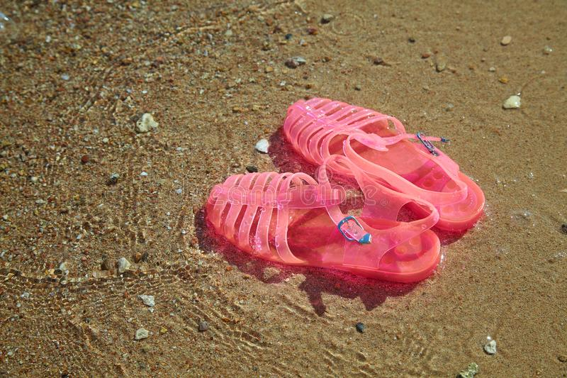 Pink Women`s JELLY SANDALS on a sea shore. LADIES FLAT JELLIES SUMMER BEACH SHOES. Sand background royalty free stock photo