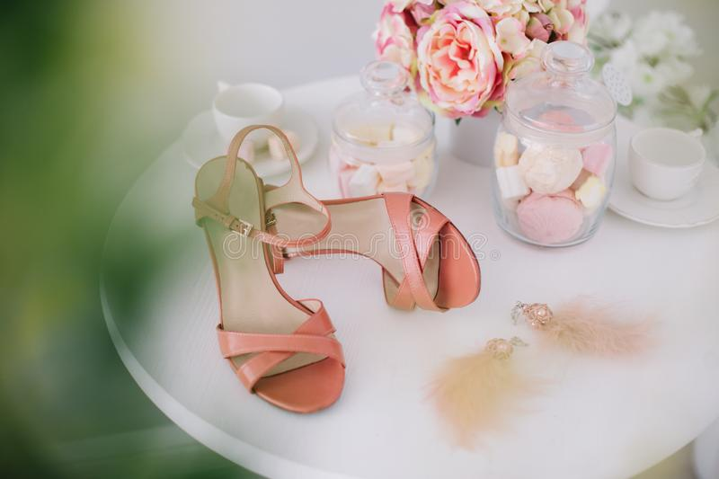 Pink women shoes, a bouquet of spring flowers and marshmallows on white background. Morning of the bride. royalty free stock photo