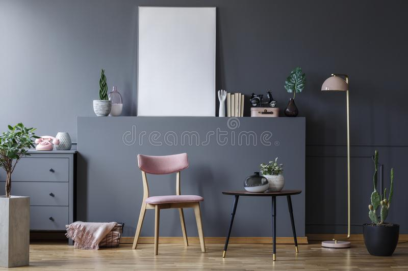 Pink wooden chair at black table in grey living room interior with mockup of empty poster royalty free stock photos