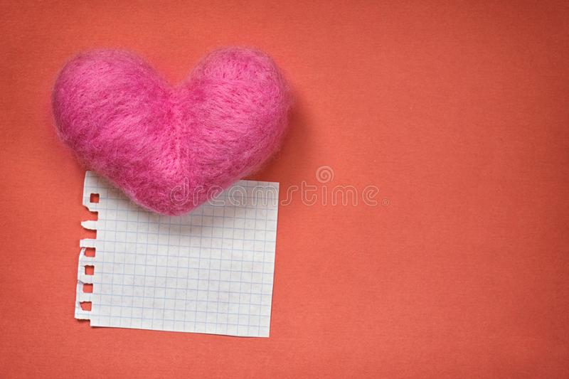 Pink wool toy heart lying with a clean notepad sheet on the orange paper background royalty free stock image