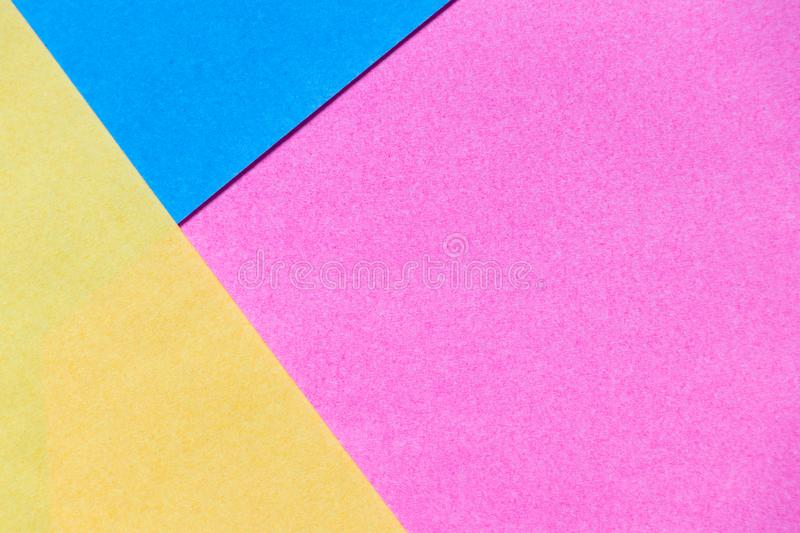 Pink, yellow and blue color paper display as abstract background stock image