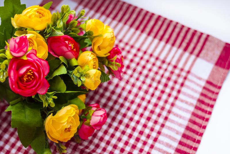 Pink-yellow bouquet of flowers on a checkered background. Festive composition. Pink-yellow bouquet of flowers on  a checkered background. Festive composition stock image