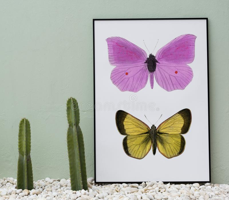 Pink and Yellow Butterflies Painting Beside Two Green Cacti royalty free stock photos