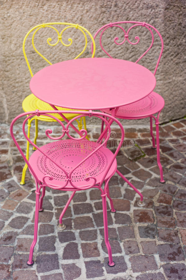 Pink and yellow chairs. Beautiful pink and yellow chairs in street cafe royalty free stock photo