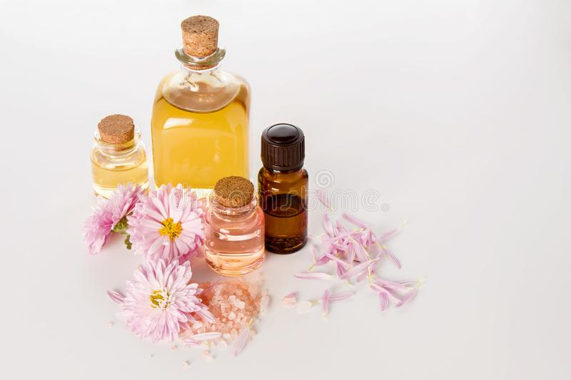 Pink and yellow essential oil and bottled water for aromatherapy and SPA on white background stock photography