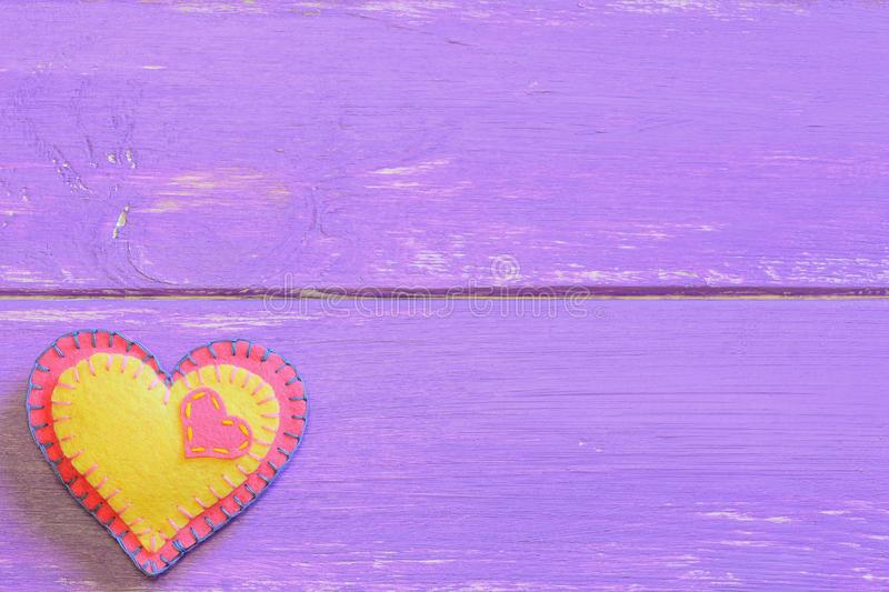 Pink and yellow felt heart on a purple wooden background with empty space for text. Felt valentine background. Valentines Day heart symbol. Valentine crafts for royalty free stock image