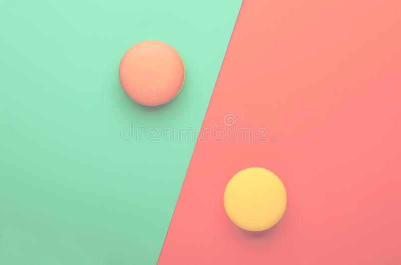 Pink yellow macaroons on blue pink graphic background, neon color, place for text, creative layout, top view royalty free stock photography