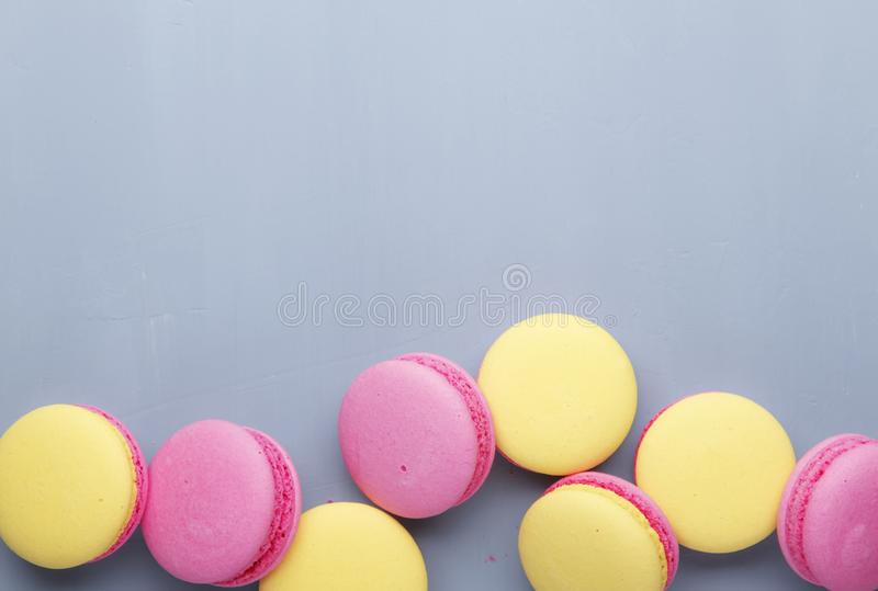 Pink yellow macaroons cake on gay background, neon color, place for text, creative layout, top view. Pink yellow macaroons cake on gay background, neon color stock images