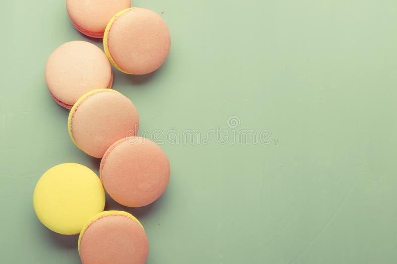 Pink yellow macaroons cake on pastel green background, neon color, place for text, creative layout, top view. Pink yellow macaroons cake on pastel green royalty free stock photo