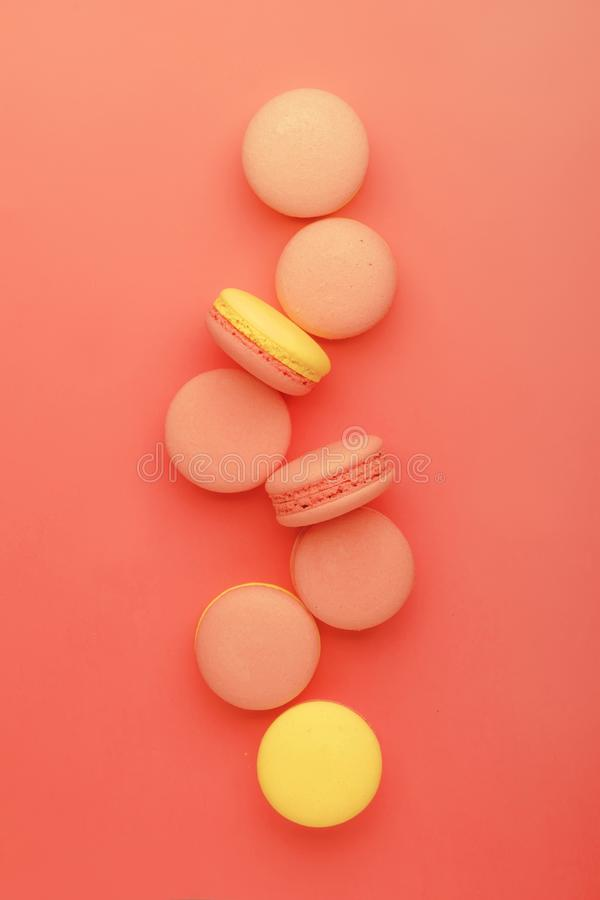 Pink yellow macaroons on coral pink graphic background, neon color, place for text, creative layout, top view stock image