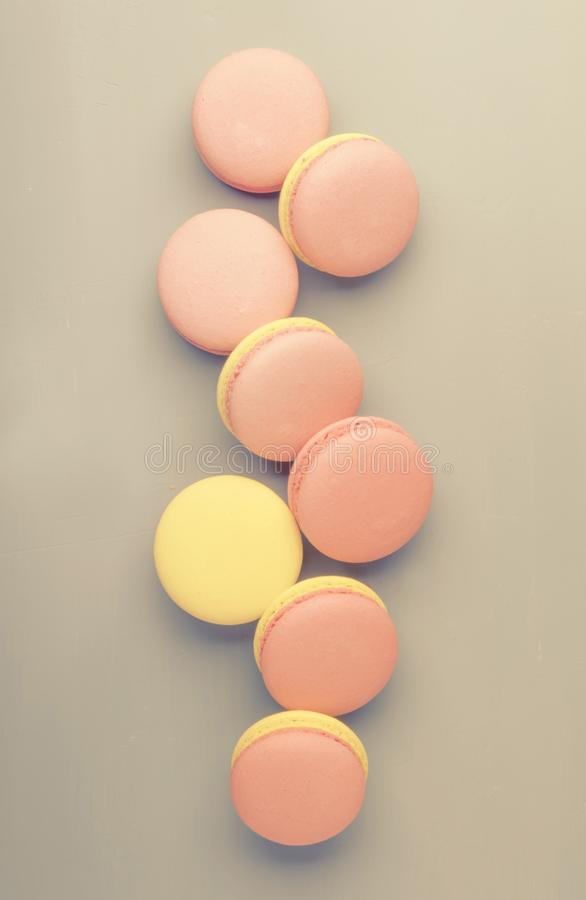 Pink yellow macaroons on gray graphic background, pastel color, place for text, creative layout, top view. Pink yellow macaroons on gray graphic background royalty free stock images