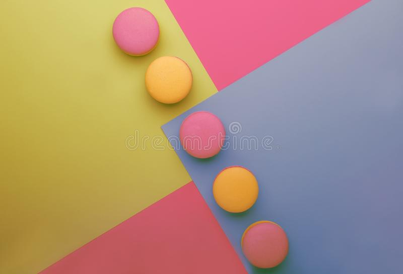 Pink yellow macaroons on yellow blue pink graphic background, neon color, place for text, creative layout, top view stock photo