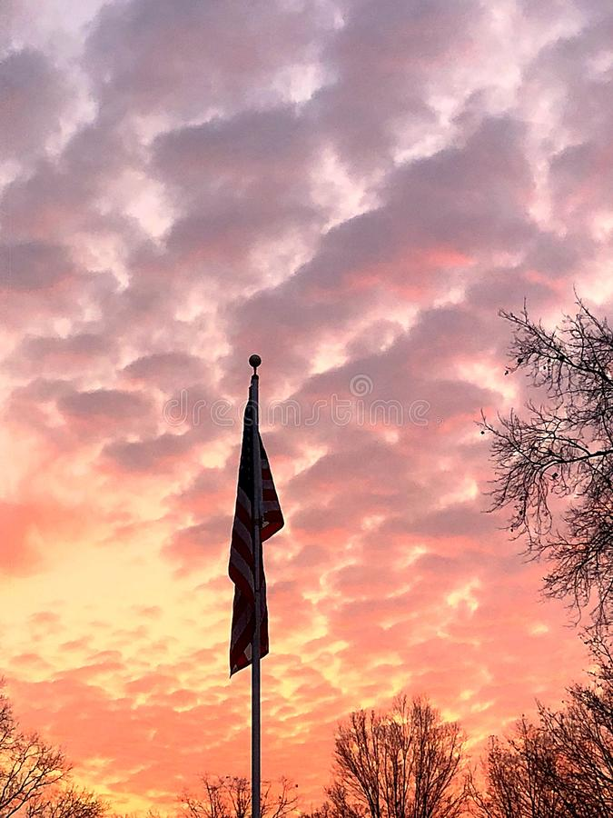 Pink and yellow sunrise with America flag royalty free stock image