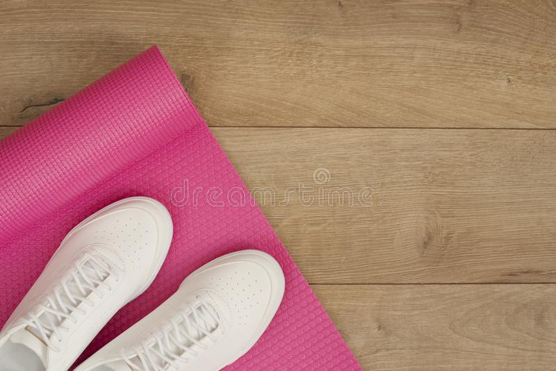 Pink yoga mat and white trendy sneakers on a wooden background. Fitness concept, active lifestyle, body care concept. Wood Backgro royalty free stock image