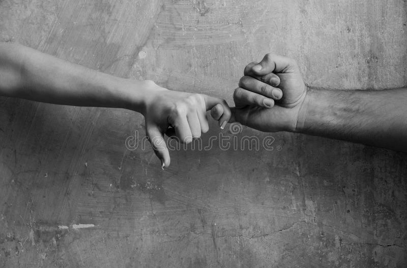 Male and female hands touching each other with little fingers. Pinkie promise and friendship. Male and female hands touching each other with little fingers on stock image