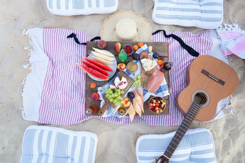 Pinkin na plaży przy zmierzchem w stylowym boho, jedzenia i napoju poczęciu, zdjęcie stock