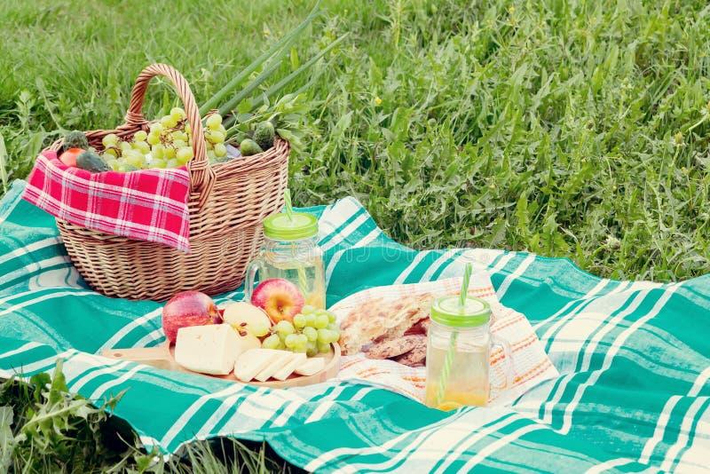 Pinkin na trawie na letnim dniu poj?cie lata plenerowy odtwarzanie - kosz, winogrona, ser, chleb, jab?ka - fotografia stock
