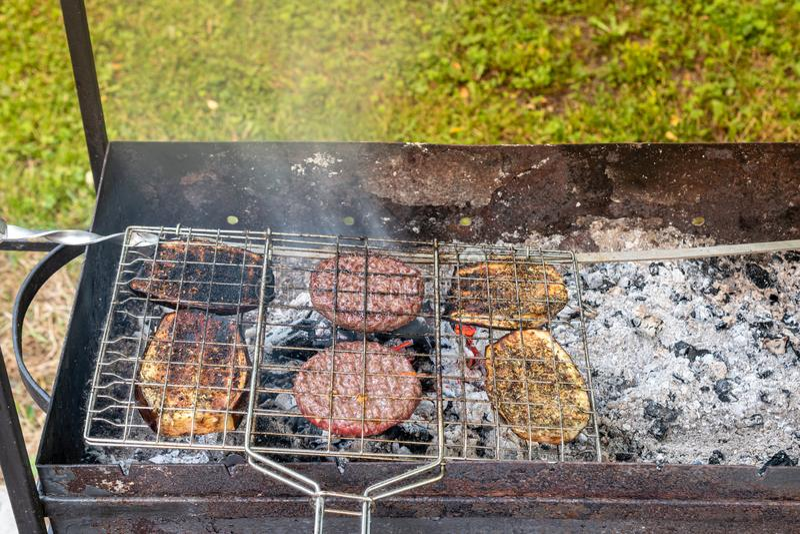 Pinkin w wiosce Smażyć hamburgery i oberżynę na grillu fotografia stock