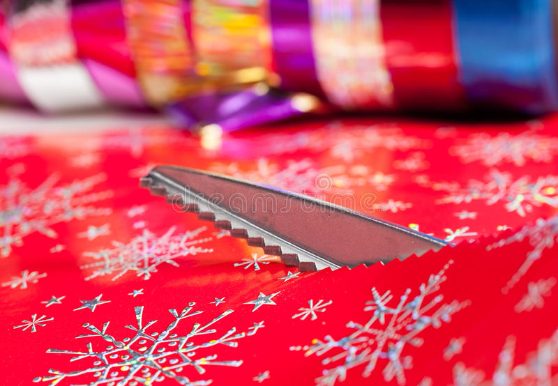 Pinking shears or scissors cutting. Christmas paper being cut by special scissors to create pattern in the cut edge royalty free stock images