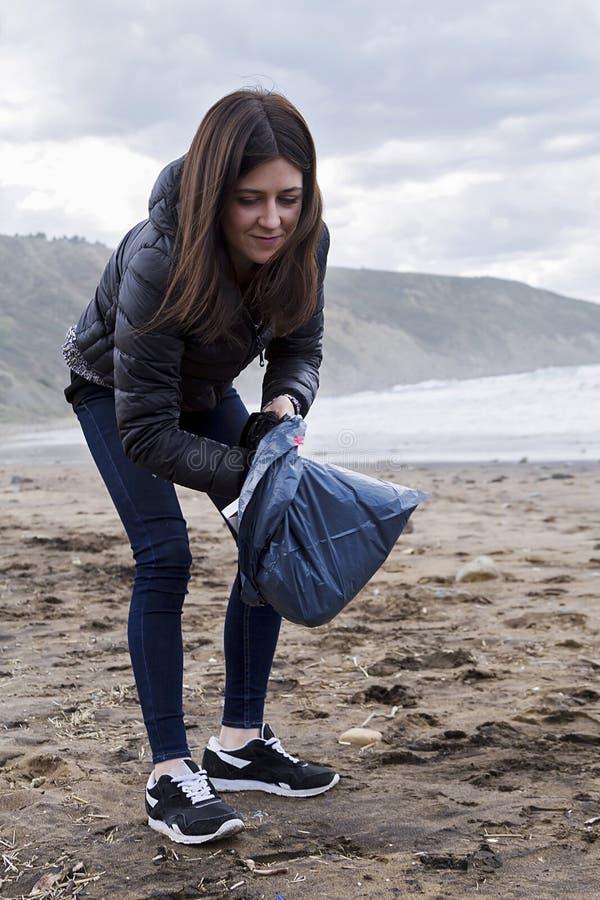Pinking upp avskräde i stranden royaltyfria foton