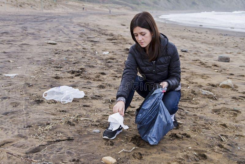 Pinking upp avskräde i stranden royaltyfri fotografi