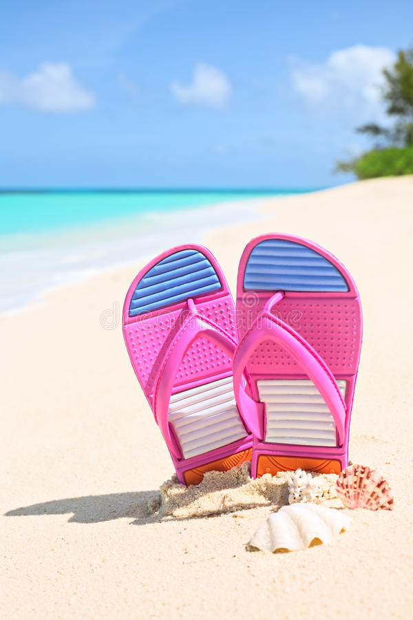 Pinks flip-flops on a sunny sandy beach.Tropical beach vacation. Pinks flip-flops on a sunny sandy beach.nTropical beach vacation and travel concept, vertical royalty free stock photography