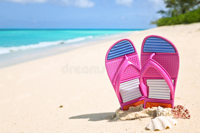 Pinks flip-flops on a sunny sandy beach.Tropical beach vacation. Pinks flip-flops on a sunny sandy beach. Tropical beach vacation and travel concept stock images