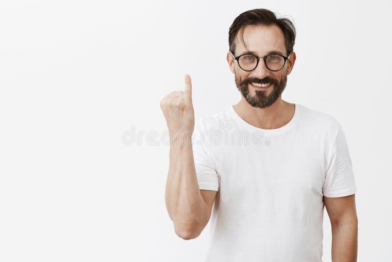 pinky присягните Портрет дружелюбного очаровательного взрослого человека в стильных стеклах и белой футболке показывая палец и ус стоковые изображения rf