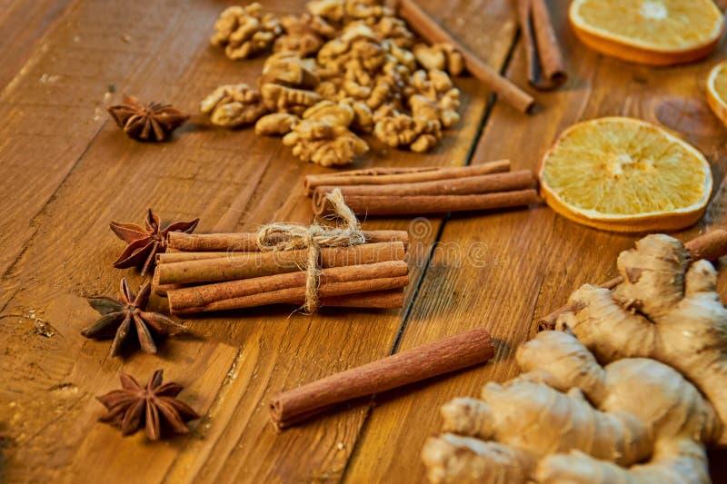 Pinnar av kanel- och anisstjärnor på träbrun bakgrund Ingredienser för funderat vin: torkade frukter, apelsin, ingefära, kanel royaltyfri bild