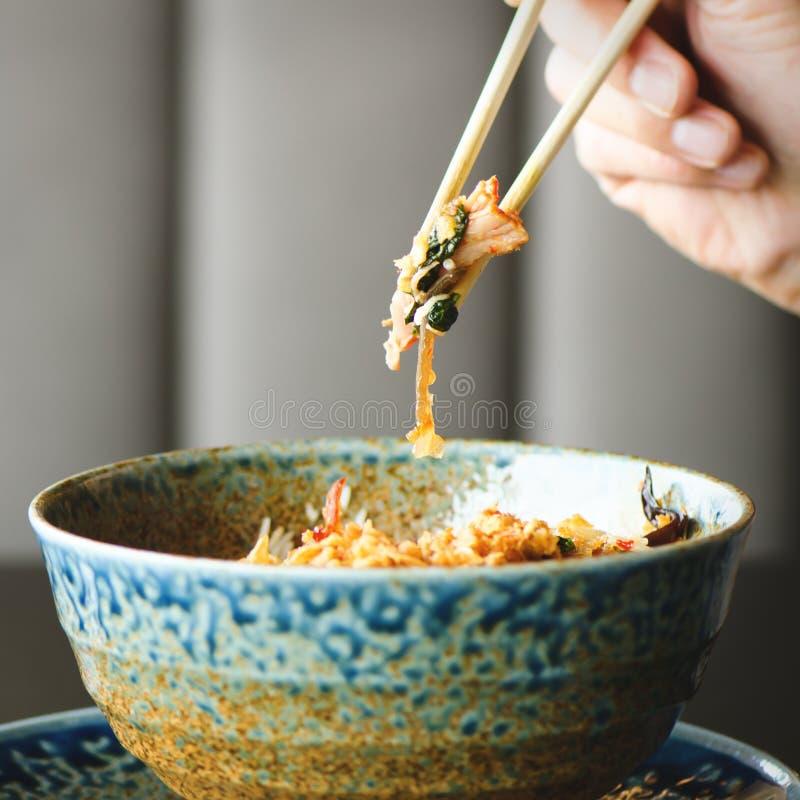 Pinnar för hand för man` s hållande över en platta av japan, thai kinesiskt mål - ris, champinjon, grönsaker Cafe arkivfoton