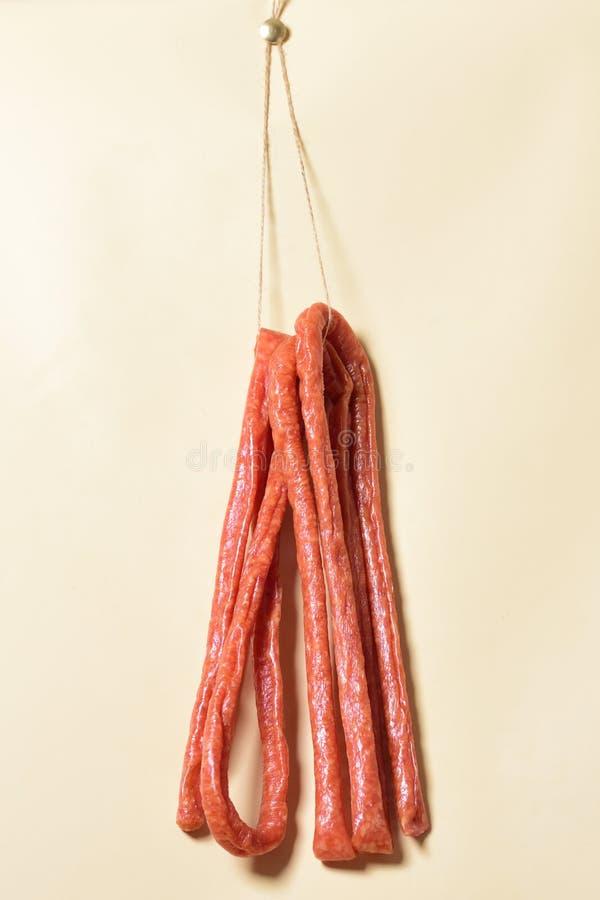Pinnar salami eller korvar som hänger på repen arkivbilder
