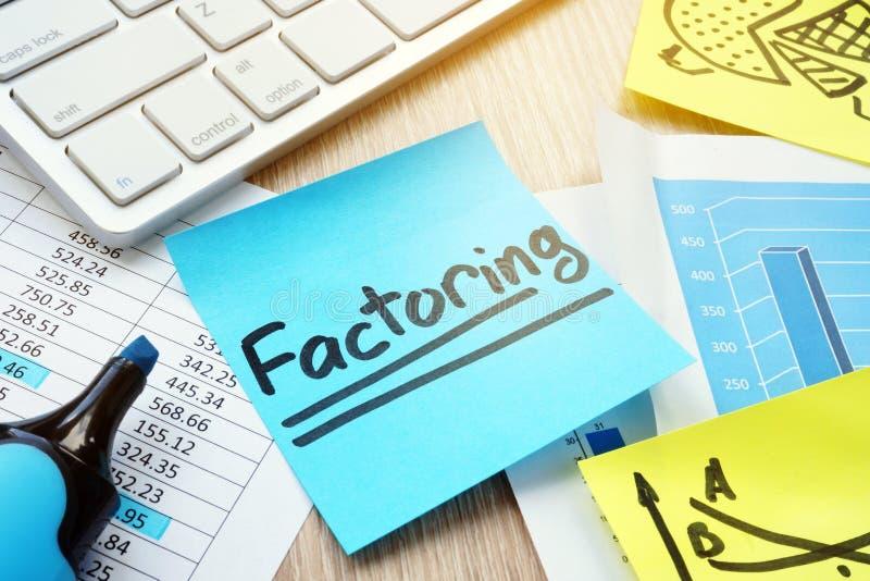 Pinne med ordet som dela upp i faktorer på ett skrivbord Faktorbegrepp arkivbild