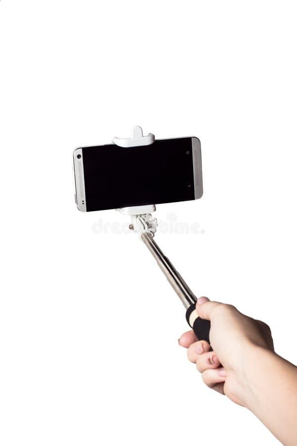 Pinnen för selfie för handinnehavtelefonen isolerade den vita snabba banan inom royaltyfria foton