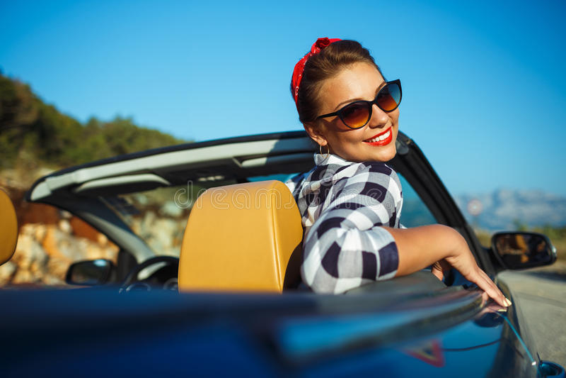 Pino bonito acima da mulher que senta-se no cabriolet, apreciando a viagem no lu fotografia de stock