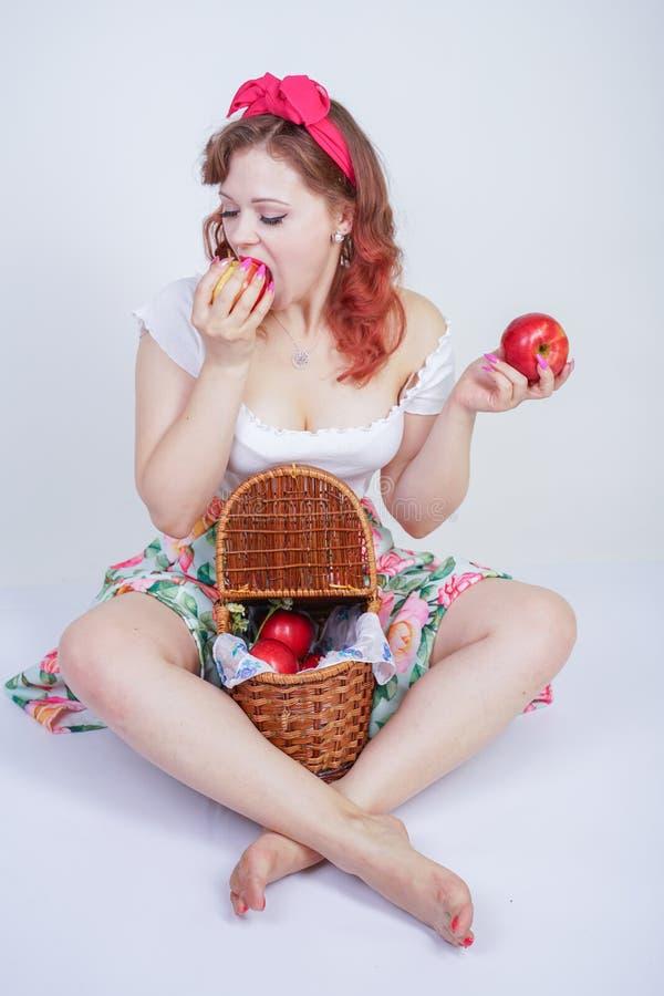 Pino bonito acima do levantamento feliz da moça caucasiano com maçãs vermelhas senhora bonito do vintage no vestido retro que tem foto de stock