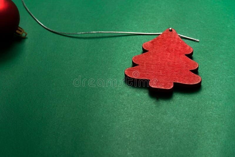 Pino di legno rosso albero di Natale e palla ornamentale per le feste su carta verde sfondo tradizionale per le festività immagini stock libere da diritti