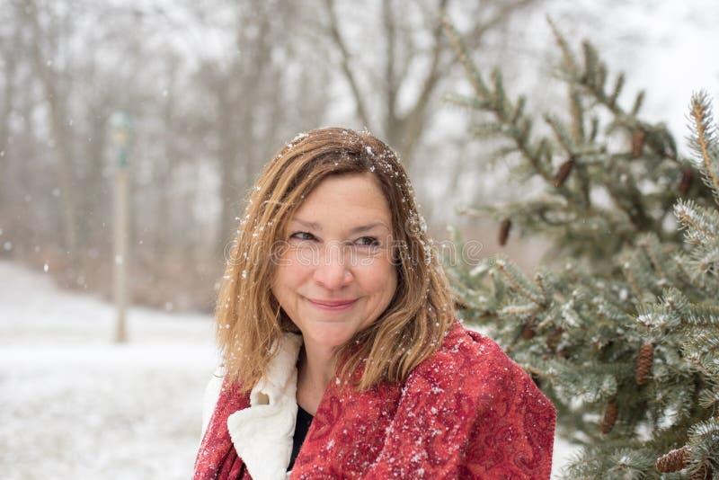 Pino facente una pausa della donna felice in parco mentre la neve magica è fotografia stock