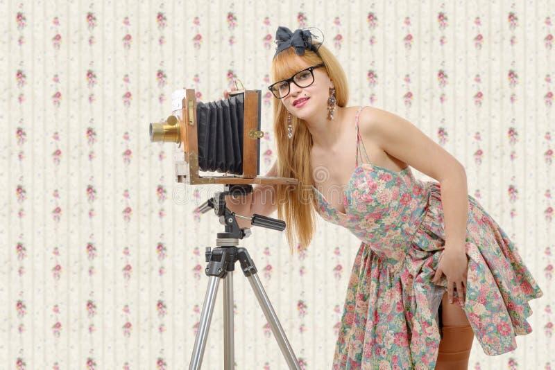 Pino 'sexy' acima da menina com a câmera de madeira velha da foto imagens de stock royalty free