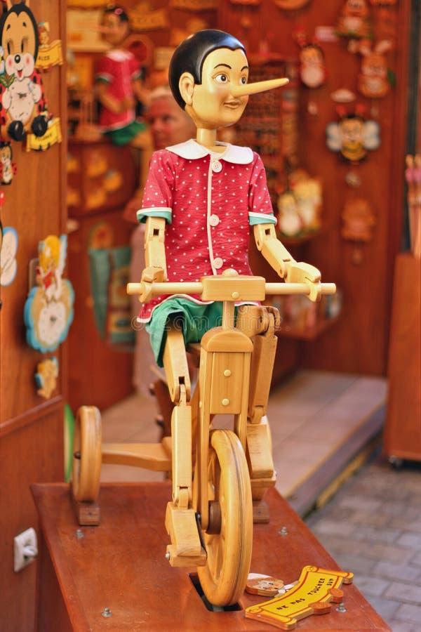 Pinocchio auf einem hölzernen Fahrrad stockfotos