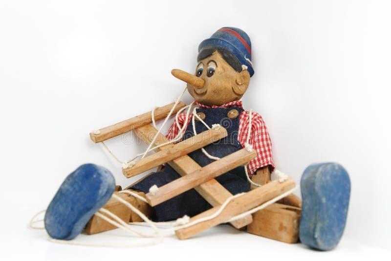 Pinocchio che si siede sul bianco fotografia stock libera da diritti